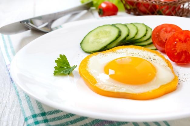 Жареное яйцо в кругу сладкого перца на белой тарелке со свежими овощами на белом фоне деревянные.