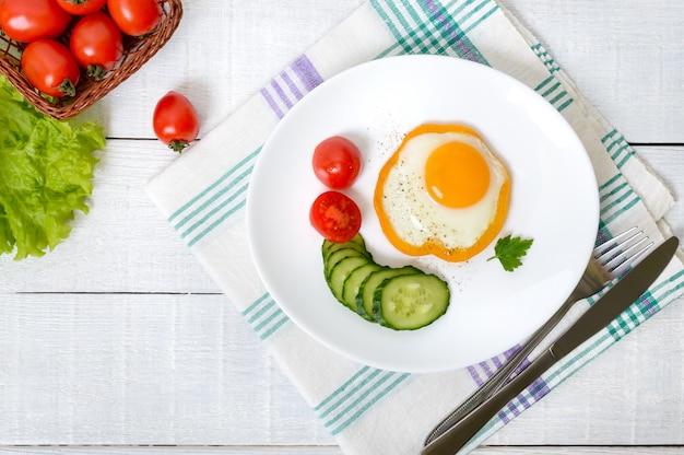 白い木製の背景に新鮮な野菜と白い皿にピーマンの輪で目玉焼き。