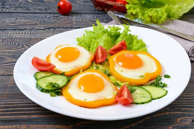 Жареное яйцо в кругу сладкого перца на белой тарелке со свежими овощами на деревянном фоне.
