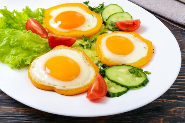 木製の背景に新鮮な野菜と白い皿にピーマンの輪で目玉焼き。
