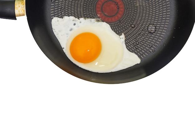 白のフライパンで目玉焼き。上面図。フライパンの一部