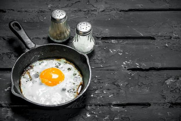 프라이팬에 튀긴 계란. 검은 소박한 배경.