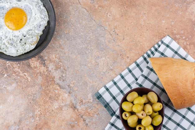 Жареное яйцо на сковороде, подается с зелеными маринованными оливками