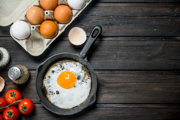 신선한 계란의 카세트와 함께 냄비에 튀긴 계란. 나무 배경.