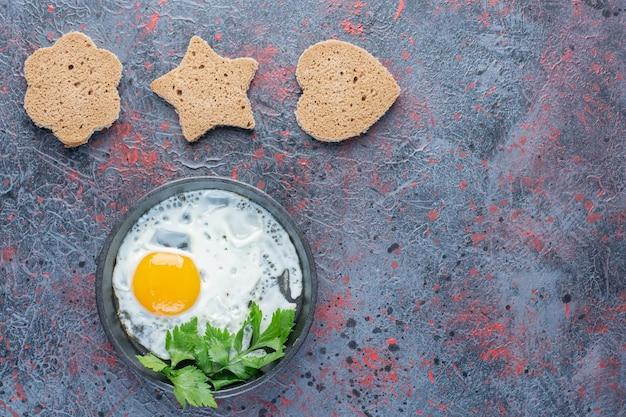 Жареные яйца на сковороде с базиликом и ломтиками хлеба.