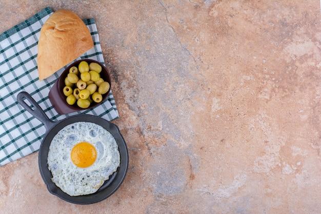 Жареное яйцо на сковороде с зелеными оливками и хлебом