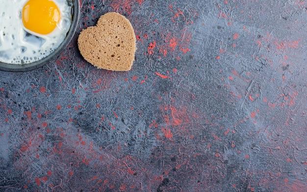 Жареные яйца на сковороде с ломтиками хлеба в форме сердца в сторону.