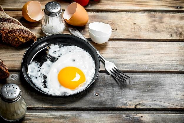호밀 빵과 함께 냄비에 튀긴 계란. 나무 배경.