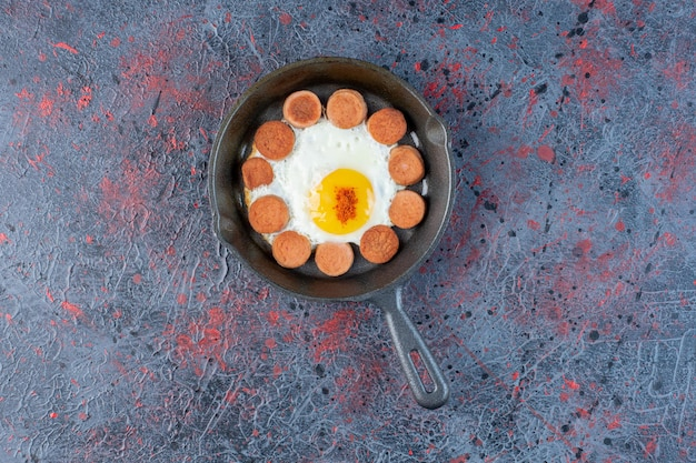 프라이팬에 소시지와 함께 계란 프라이.