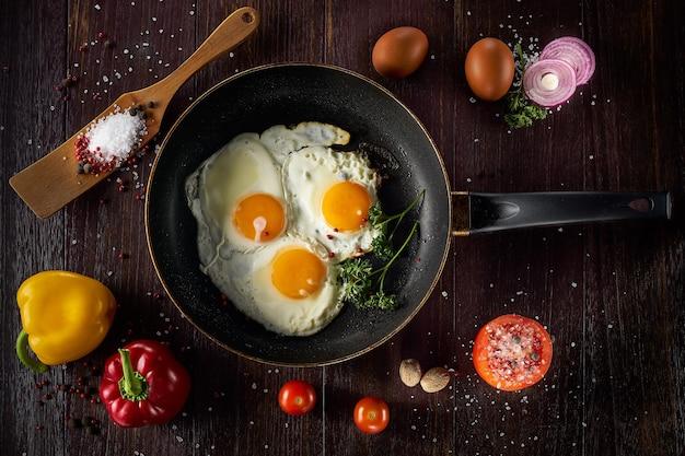 野菜と鍋で目玉焼き。茶色の素朴な背景に。高品質の写真