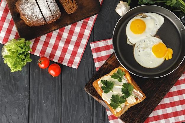 Жареное яйцо в сковороде с нарезанным хлебом на деревянном столе