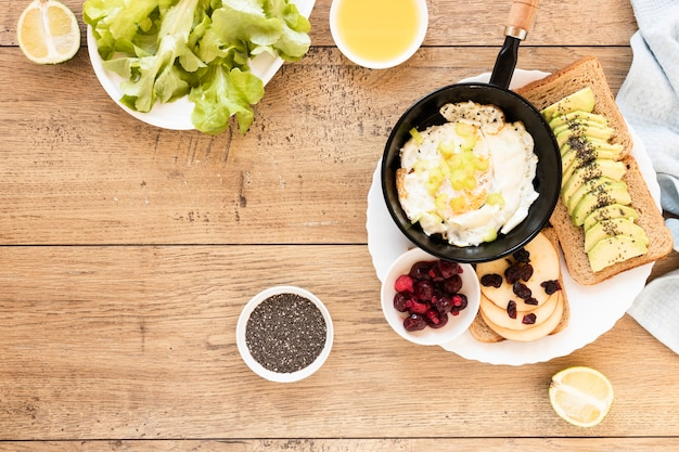 Жареное яйцо в сковороде с бутербродами с авокадо