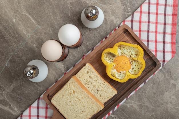 Жареное яйцо в перце и ломтиках хлеба на деревянной тарелке. фото высокого качества