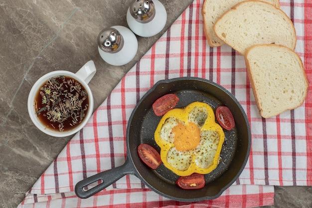 Жареные яйца в перце и помидорах на черной сковороде. фото высокого качества