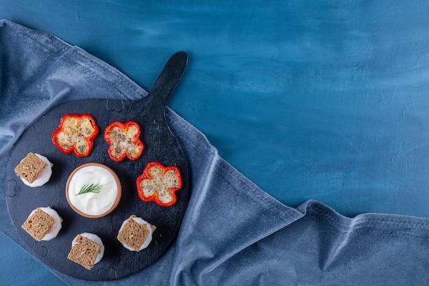Жареные яйца в перце рядом с нарезанным хлебом на разделочной доске на полотенце, на синем.
