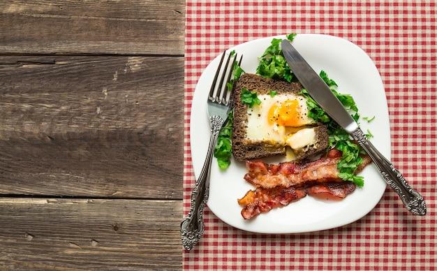 베이컨과 소박한 나무 바탕에 파 슬 리와 호 밀 빵에 튀긴 계란. 평면도.