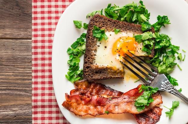 소박한 나무 표면에 베이컨과 파 슬 리와 호밀 빵에 튀긴 계란. 평면도.