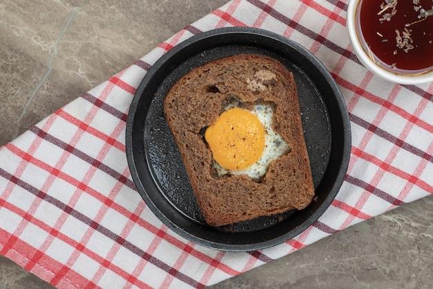 黒皿とお茶の黒パンスライスの中の目玉焼き。高品質の写真