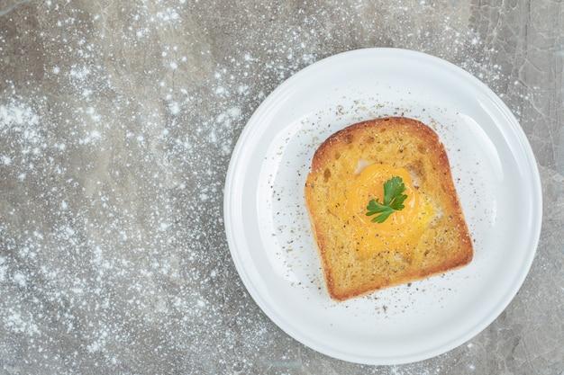 하얀 접시에 토스트 빵 조각 안에 튀긴 계란. 고품질 사진