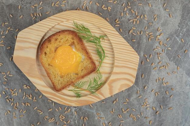 Жареное яйцо внутри ломтика тостового хлеба на деревянной тарелке. фото высокого качества