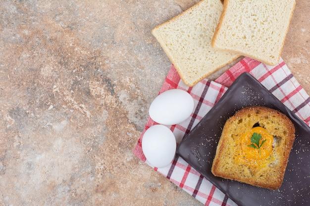 パンのスライスと黒いプレートのトーストの中の目玉焼き
