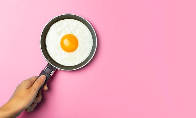 튀긴 계란은 빈 분홍색 배경의 창의적인 아침 식사에 프라이팬에 최소한의 튀긴 계란입니다