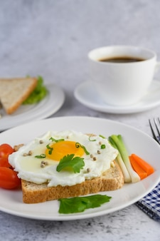 A fried egg laying on a toast, topped with pepper seeds with carrots and spring onions.