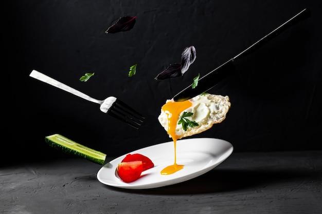 계란후라이 공중부양. 어두운 음식 사진입니다. 액체 노른자, 바질 잎, 딜, 오이가 있는 닭고기 달걀이 하얀 접시에 떨어집니다. 아침 창조적 인 개념입니다.