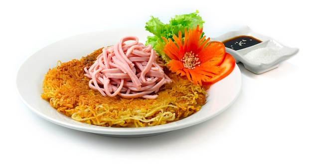 Fried egg noodles with pork and in a white plate with soy sauce isolated on white background