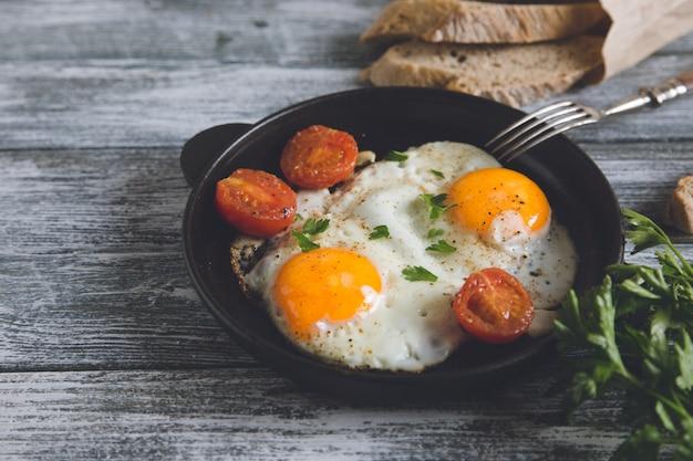 Жареное яйцо на сковороде с помидорами черри и петрушкой
