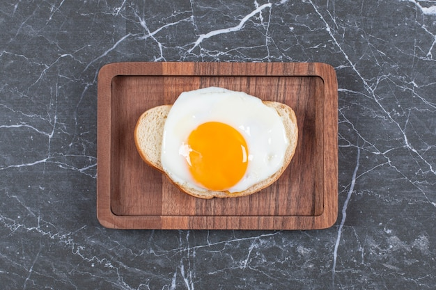 Жареные яйца на хлебе, нарезанном на доске, на мраморной поверхности