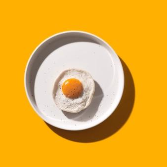 Жареное яйцо на белом фоне на желтый с тенями.