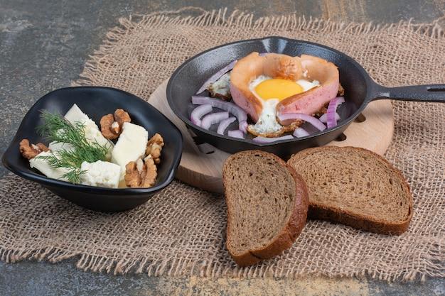 Uovo fritto in padella e ciotola di formaggio con noccioli di noce.
