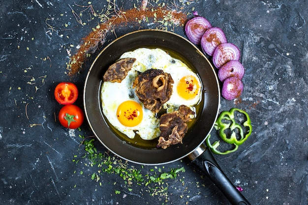Fried egg in a pan with beef meat, with sliced green pepper, tomatoes an onions