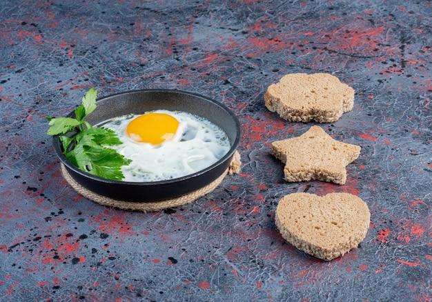 Uovo fritto in padella con fette di pane a forma di cuore a parte.