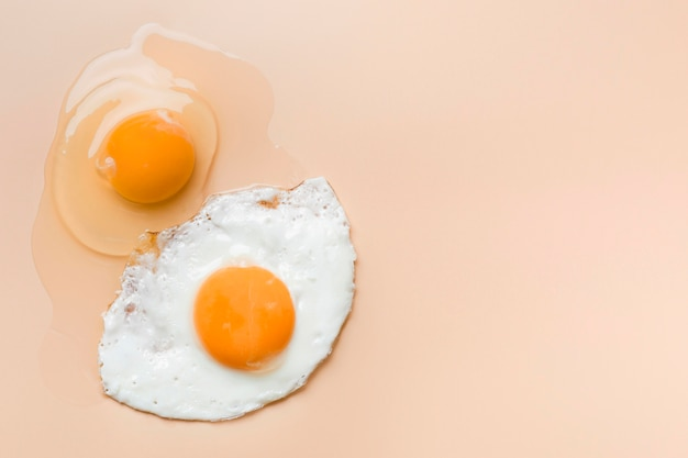 Fried egg and raw egg yolk with copy-space