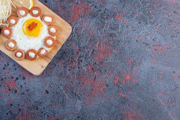Uovo fritto servito con salsiccia alla griglia e spezie su un piatto di legno.