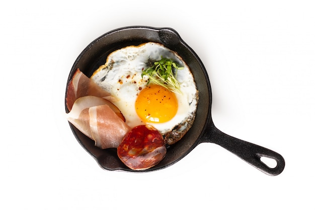 Fried egg in skillet iron pan with flax sprouts and bacon with copy space