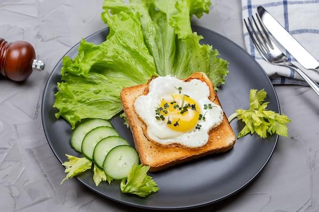 통밀 토스트에 계란 후라이를 얹고 샐러드와 화이트 머스타드 마이크로 그린을 얹습니다. 계란과 채소로 토스트하십시오.