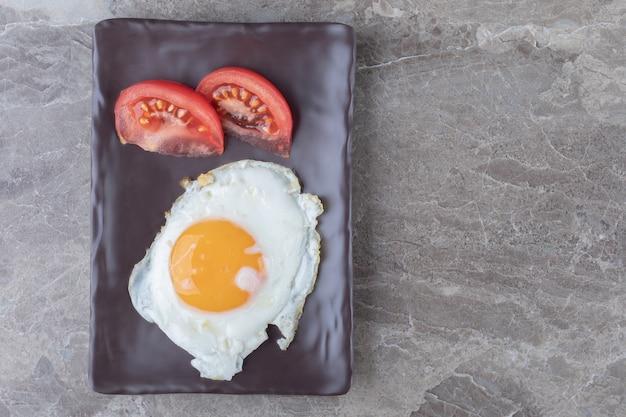 Uovo fritto e fette di pomodoro sul piatto scuro.