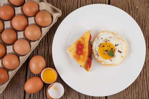 Uovo fritto su un piatto bianco con pane tostato, cipollotto affettato e pomodori a fette