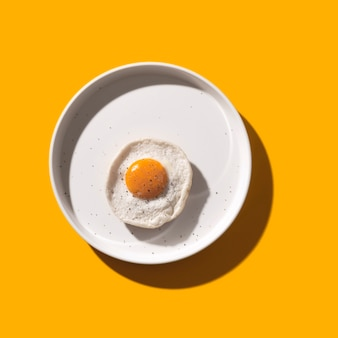 Fried egg on white plate on yellow with shadows.