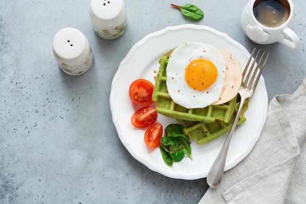 ライトグレーのコンクリートテーブルの白いセラミックプレートにチーズ、トマト、フダンソウ、ほうれん草のワッフルを添えた目玉焼き。朝食のサンドイッチ。セレクティブフォーカス。上面図。スペースをコピーします。