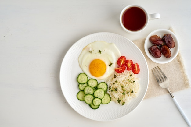 Fried egg with cherry tomatoes and cucumber on light white