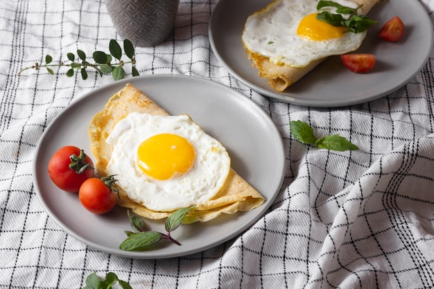 Fried egg with crepe and tomatoes
