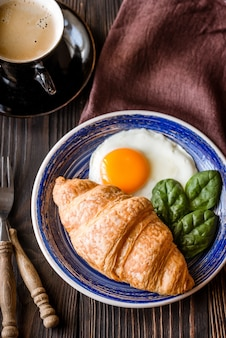 Fried egg with croissant and a cup of coffee