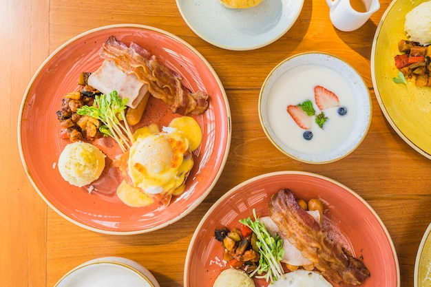 Fried egg with eggs benedict and omelette around bacaon ham sausage in plate