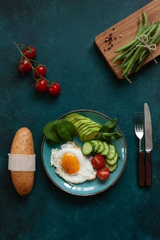 Fried egg with fresh vegetables and bread on concrete green background.