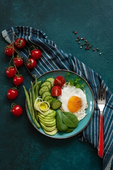 Fried egg with fresh vegetables on green background.