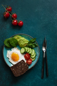 Fried egg with fresh vegetables and rye bread on concrete green background.